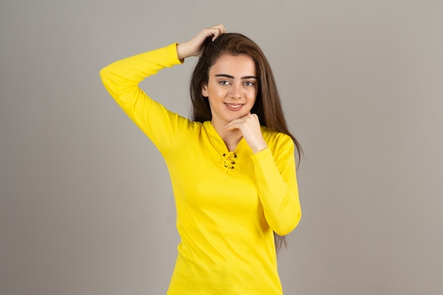 Portrait of young girl in yellow top standing on gray wall.