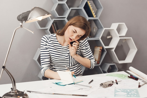 Portrait of young good-looking european girl with brown hair in striped clothes talking on phone with customer, writing down details of work in notebook with unsatisfied face expression.