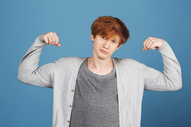 Portrait of young good-looking guy with ginger hair in casual gray clothes playing muscles,  with unsure and confused expression, feeling uncomfortable.