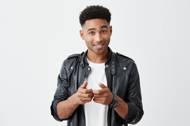 Ritratto di giovane bello studente maschio dalla pelle abbronzata con l'acconciatura afro in abito elegante casual gesticolando con le mani, mostrando all'amico che vuole giocare ai giochi per console nel tempo libero.