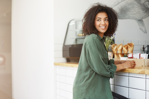 Portrait of young good-looking thick-skinned student woman with curly hair in casual fashionable clothes looking aside, smiling brightfully to friend outside, waiting for her order in coffee shop. life