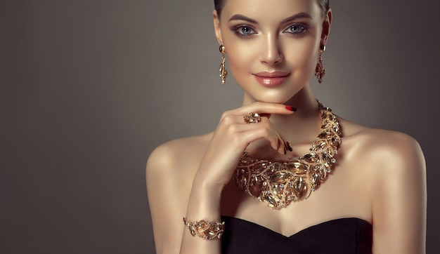 Portrait of young gorgeous woman dressed in a jewelry set of necklace, ring, bracelet and earrings. pretty blue eyed model is demonstrating an attractive makeup and manicure.