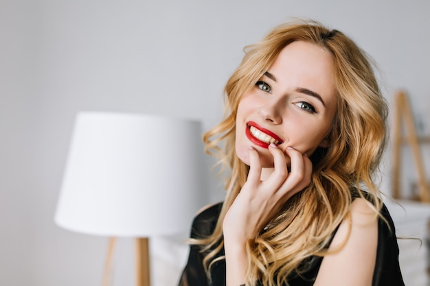 Portrait of young gorgeous woman with beautiful smile, red lips, day makeup, sensually touching her face in white room. she has long blonde wavy hair. wearing black blouse.
