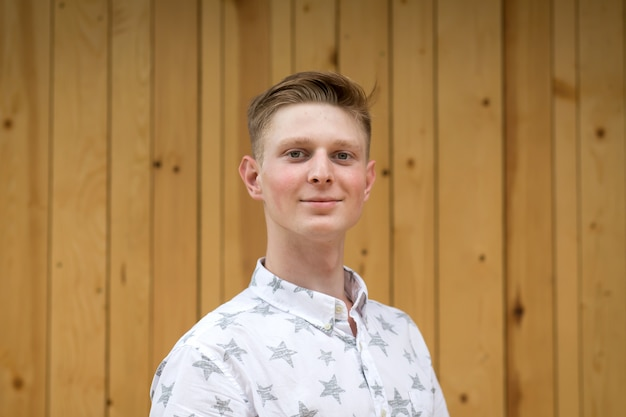 Portrait of a young guy blond on a background of wooden boards
