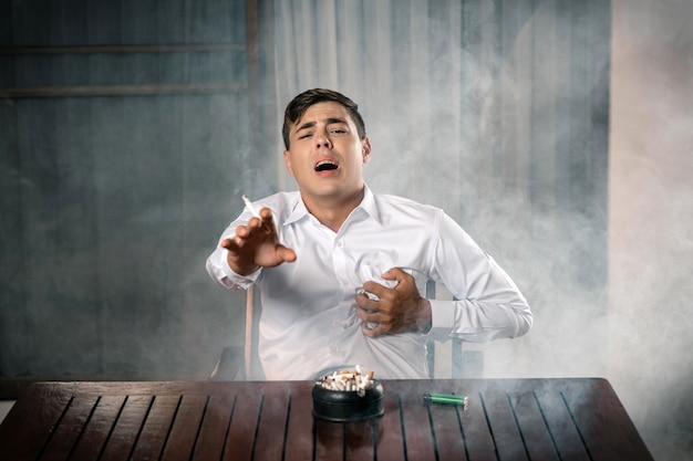 Portrait of a young guy posing, sitting at a table on which stands a full ashtray, holding a lit cigar in his hand, holding his heart. death from cigarettes. pain in the chest. stop.