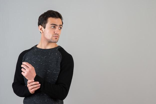 Ritratto di giovane ragazzo in piedi e guardando da qualche parte sul muro grigio
