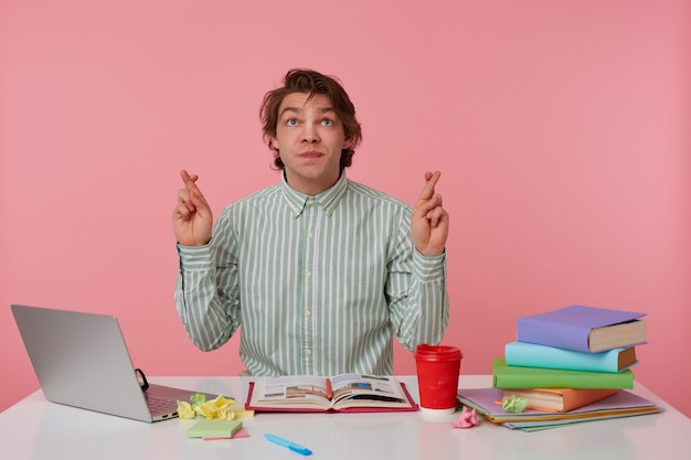 Portrait of young guy with glasses, sitting at a table with books, working at a laptop, looks up and wishes, with crossed fingers hopes for good luck, isolated over pink background.
