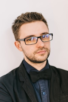Portrait of a young hairdresser in eyeglasses with a hairstyle and a tie.
