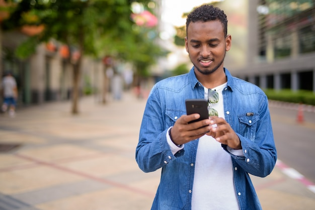 Portrait of young handsome african bearded man with afro hair exploring the city streets outdoors