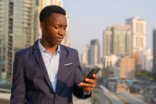 Portrait of young handsome african businessman against view of the city