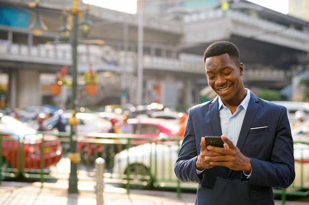 Portrait of young handsome african businessman exploring the city streets of bangkok