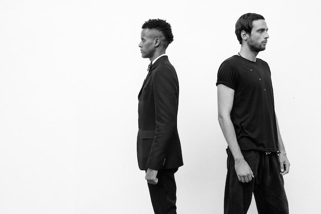 Portrait of young handsome african businessman and handsome man together against white wall in black and white