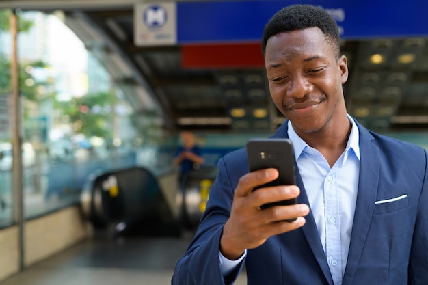 Portrait of young handsome african businessman outside the subway train station