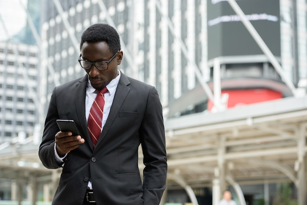 Portrait of young handsome african businessman in suit against view of modern building in the city outdoors