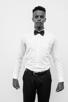 Portrait of young handsome african businessman with bow tie against white wall in black and white