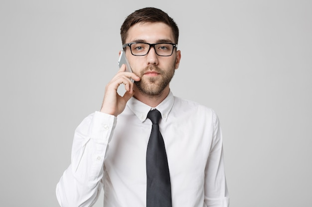 Portrait young handsome angry business man in suit talking on phone looking at camera.