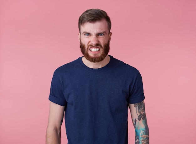 Ritratto di giovane uomo barbuto rosso arrabbiato bello in maglietta rossa, si leva in piedi su sfondo rosa, guarda la telecamera con disgusto e scopre i denti.