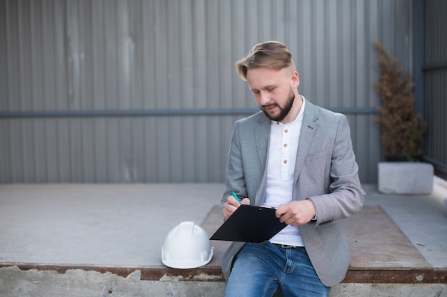 Portrait of young handsome architect writing on clipboard at outdoors