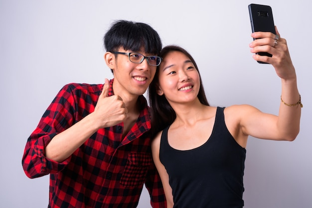 Portrait of young handsome asian man and young beautiful chinese woman together and in love against white wall
