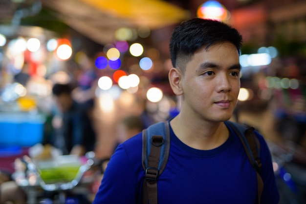 Portrait of young handsome asian tourist man exploring at chinatown in bangkok, thailand