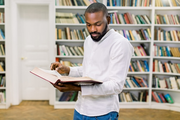 Portrait of young handsome bearded african college male student in library, reading book