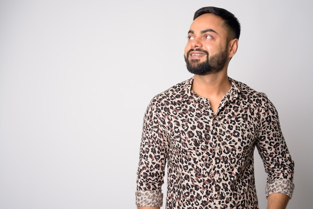 Portrait of young handsome bearded indian man against white wall
