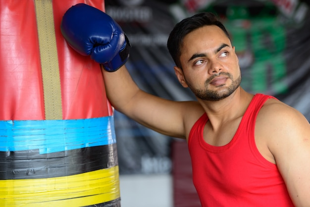 Portrait of young handsome bearded indian man exercising at the gym