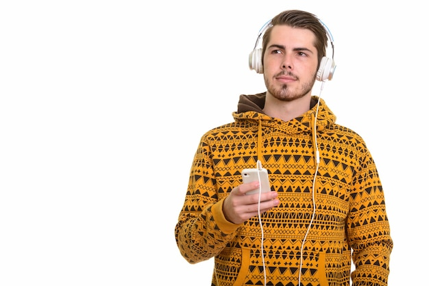 Portrait of young handsome bearded man listening to music while using phone