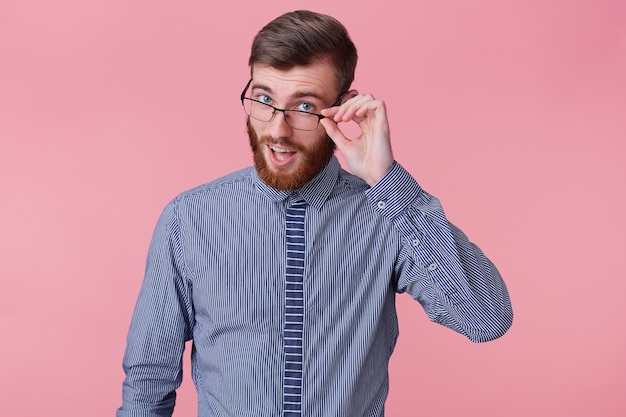 Portrait of a young handsome bearded man who tells a funny story, looks through his glasses isolated over pink background.
