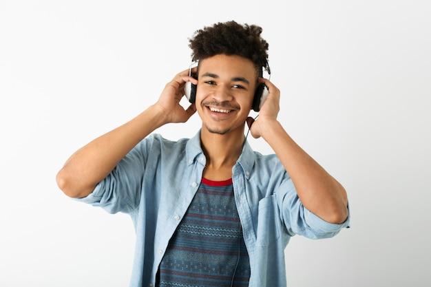 Portrait of young handsome black man listening to music on headphones on white