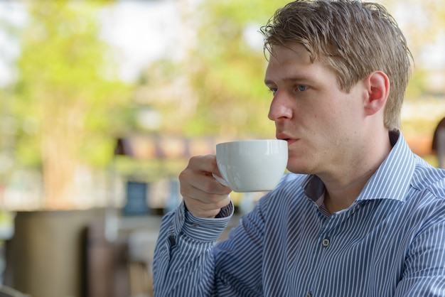 Portrait of young handsome blond businessman relaxing at the coffee shop outdoors