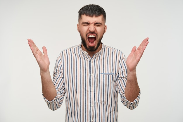 Portrait of young handsome brunette bearded male guy keeping his hands raised while screaming with wide mouth opened, wearing casual clothes while standing over white wall