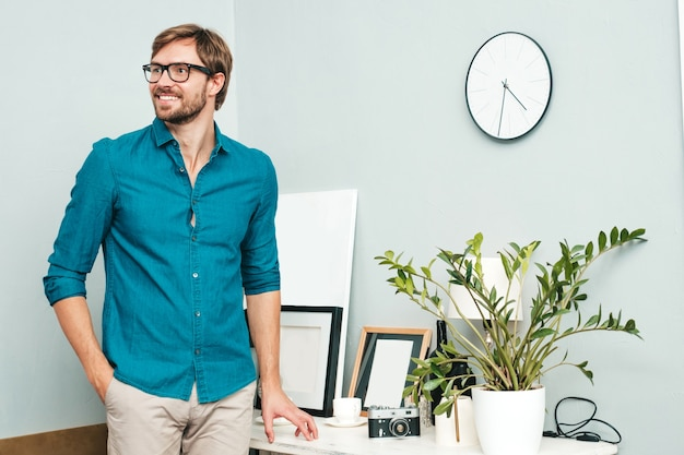 Portrait of young handsome business man. smiling male dressed in blue jeans shirt. bearded model posing at office near paper desk