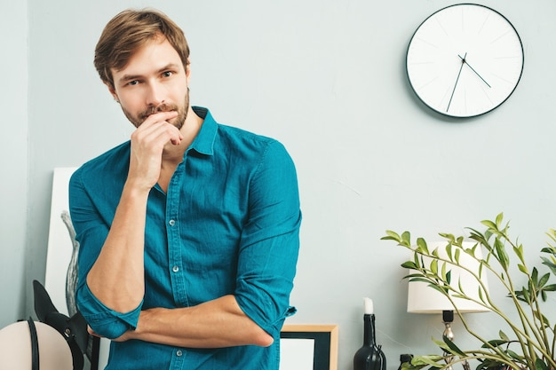 Portrait of young handsome business man. thoughtful male dressed in blue jeans shirt. bearded model posing at office near paper desk
