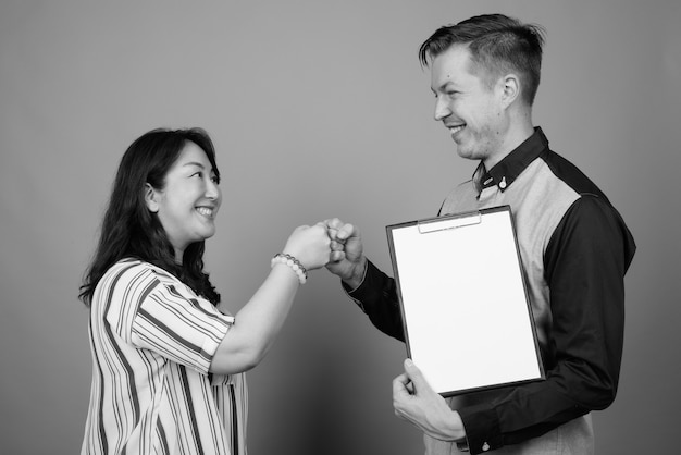 Portrait of young handsome businessman and mature asian businesswoman together with clipboard