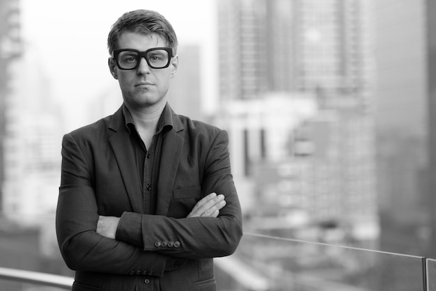 Portrait of young handsome businessman in suit against view of the city in black and white