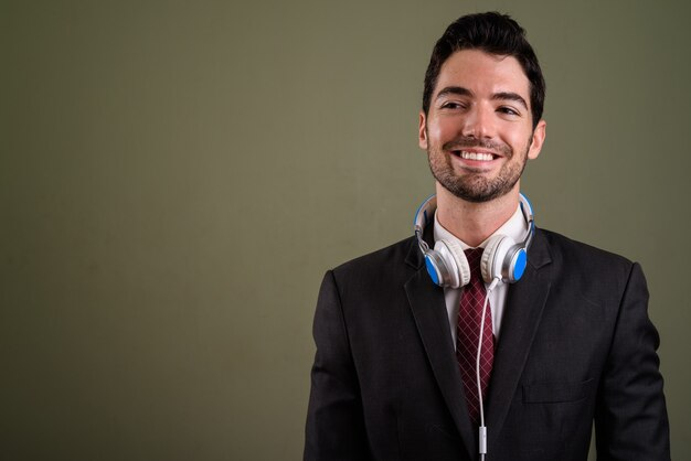 Portrait of young handsome businessman in suit with headphones