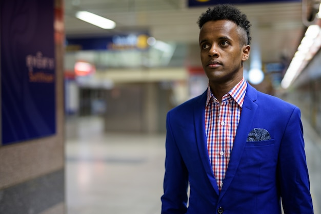 Portrait of young handsome businessman wearing suit at the subway train station in bangkok, thailand