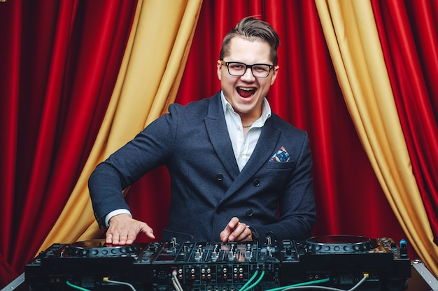 Portrait of young handsome charismatic dj in formal suit standing at mixer and smiling. fashion and nightclubbing concept