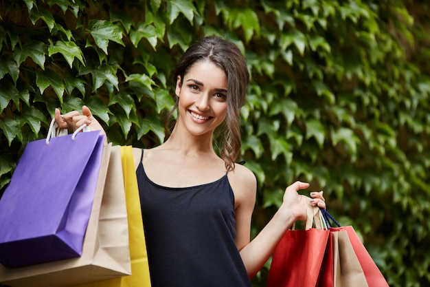 Portrait of young handsome cheerful caucasian girl with dark hair in black fashionable dress smiling brightly, looking in camera with happy expression, holding lot of colorful bags in hands after goin