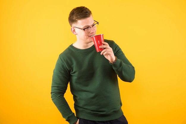 Portrait of young handsome confident guy in green sweater holding red plastic cup
