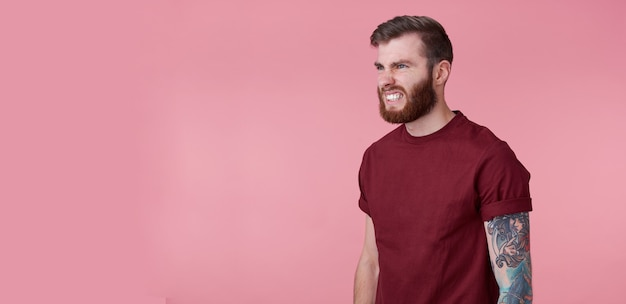Portrait of young handsome evil red bearded man in blank t-shirt, looks aggressive and shocked, stands over pink background, ooks to copy space on the left side.