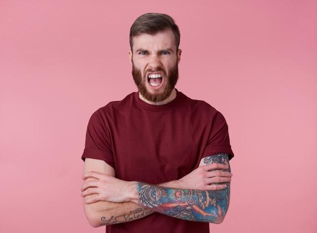 Ritratto di giovane uomo barbuto rosso diabolico bello in maglietta vuota, sembra aggressivo e scioccato, si erge su sfondo rosa e urla.