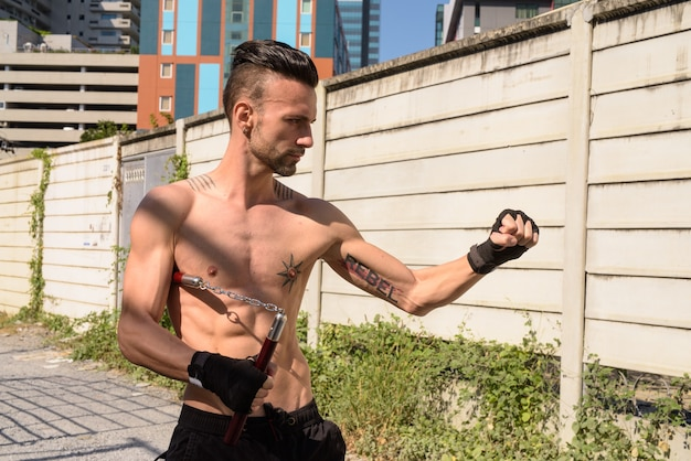 Portrait of young handsome fighter man with lean muscular body outdoors with six pack abs