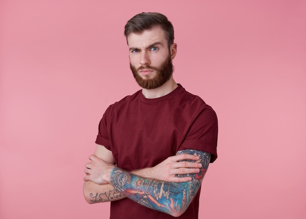 Portrait of young handsome frowning red bearded man in blank t-shirt, stands over pink background with crossed arms, looks at the camera with misunderstanding.