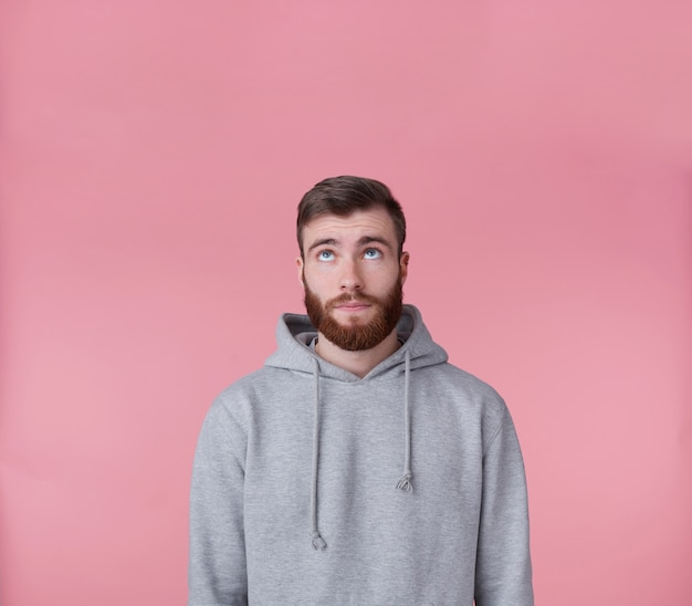 Portrait of young handsome guy looking up at the copy space and thinking about solving a problem, presents possible options, stands over pink background.