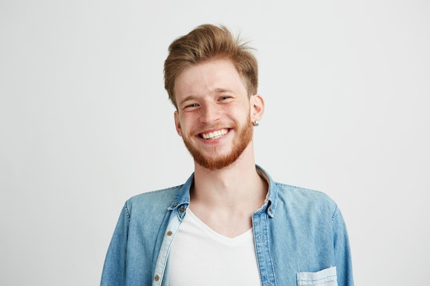 Portrait of young handsome hipster man with beard smiling laughing.