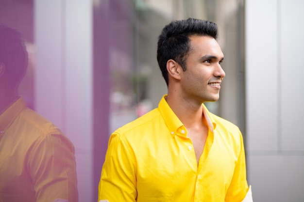 Portrait of young handsome indian man in the city streets outdoors