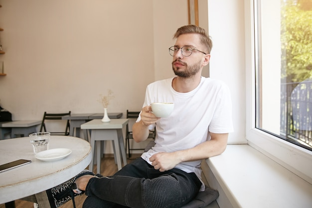 Ritratto di giovane maschio bello con la barba, indossando abiti casual e occhiali, seduto al tavolo in caffè con una tazza di caffè, aspettando qualcuno e guardando pensieroso