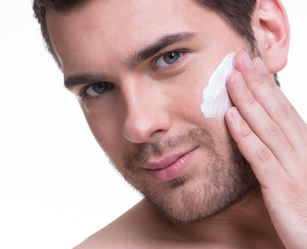 Portrait of young handsome man applying cream lotion on face - isolated on white.
